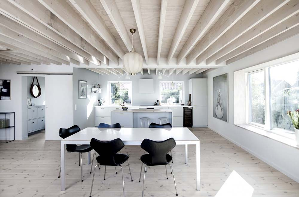 This is the dining area and the kitchen under a large wooden beamed ceiling.