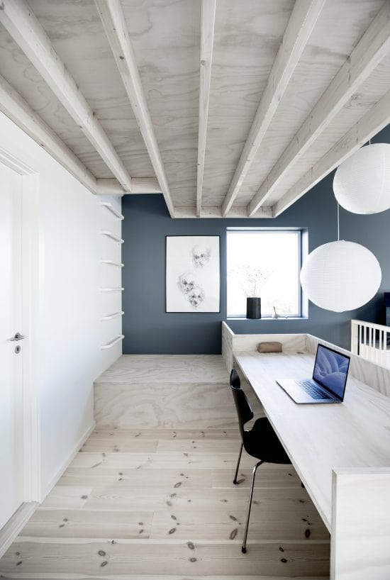 This is the home office with a built-in wooden desk that matches the hardwood flooring and the beamed ceiling.