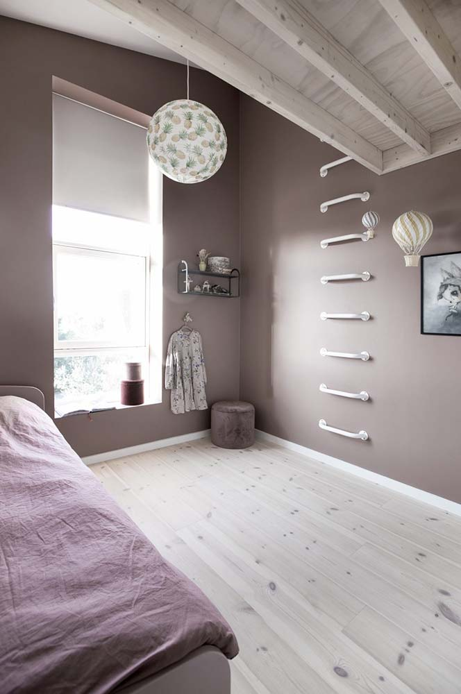 This bedroom has dark earthy walls and a set of ladder steps that lead to the loft.