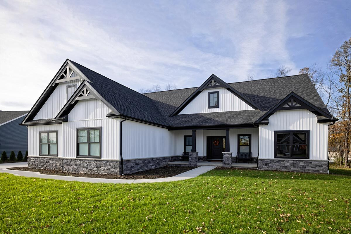 Front exterior view showing the board and batten siding, stone accents, and multiple gables adorned with black trims.