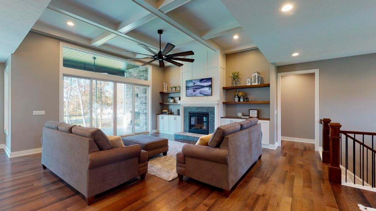 The living room has a coffered ceiling, brown sofas, a fireplace, and a clerestory window.