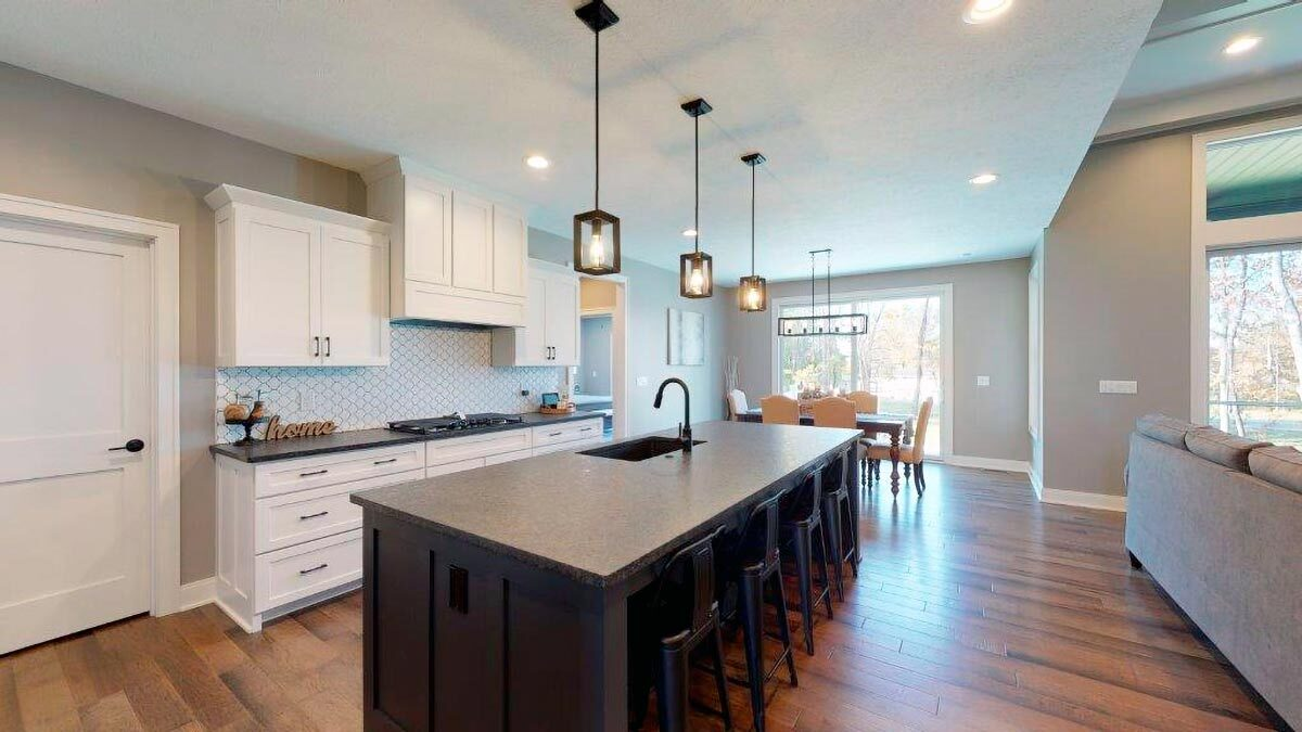 Eat-in kitchen with white cabinetry, granite countertops, and a breakfast island fitted with a sink.