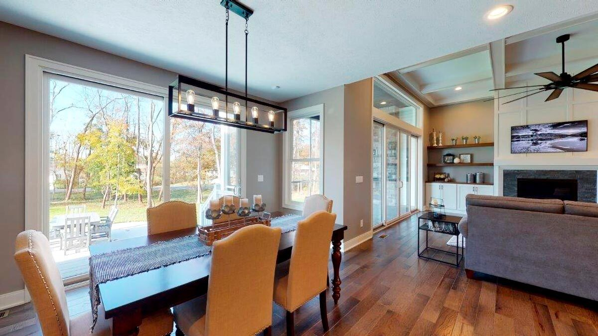 The dining room has upholstered chairs and a rectangular dining set well-lit by a linear chandelier.