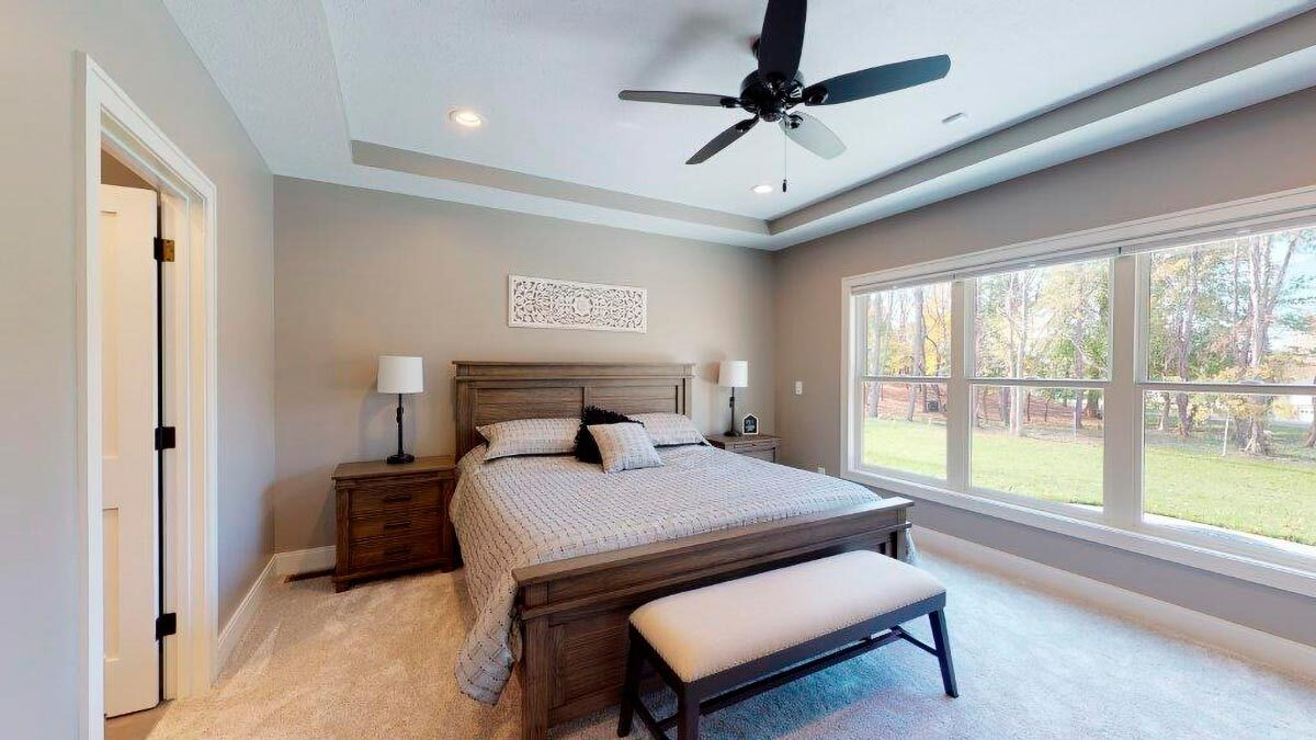 Primary bedroom with a tray ceiling, carpet flooring, and natural wood furnishings.