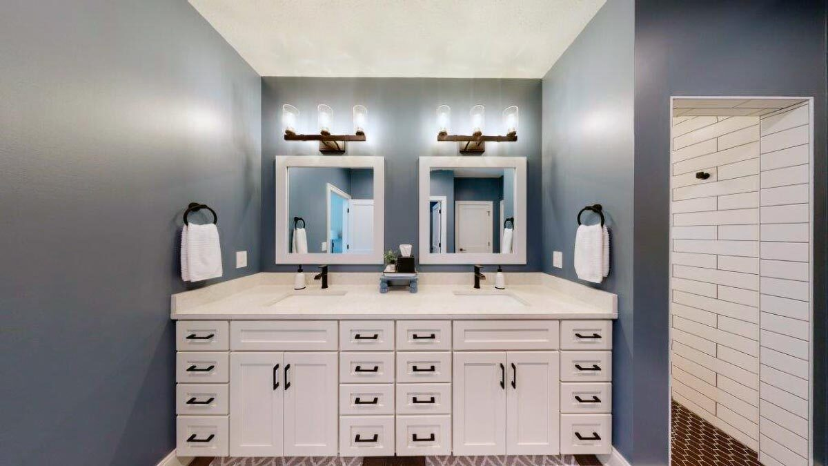 The white vanity has two undermount sinks, white cabinets, and a pair of framed mirrors.