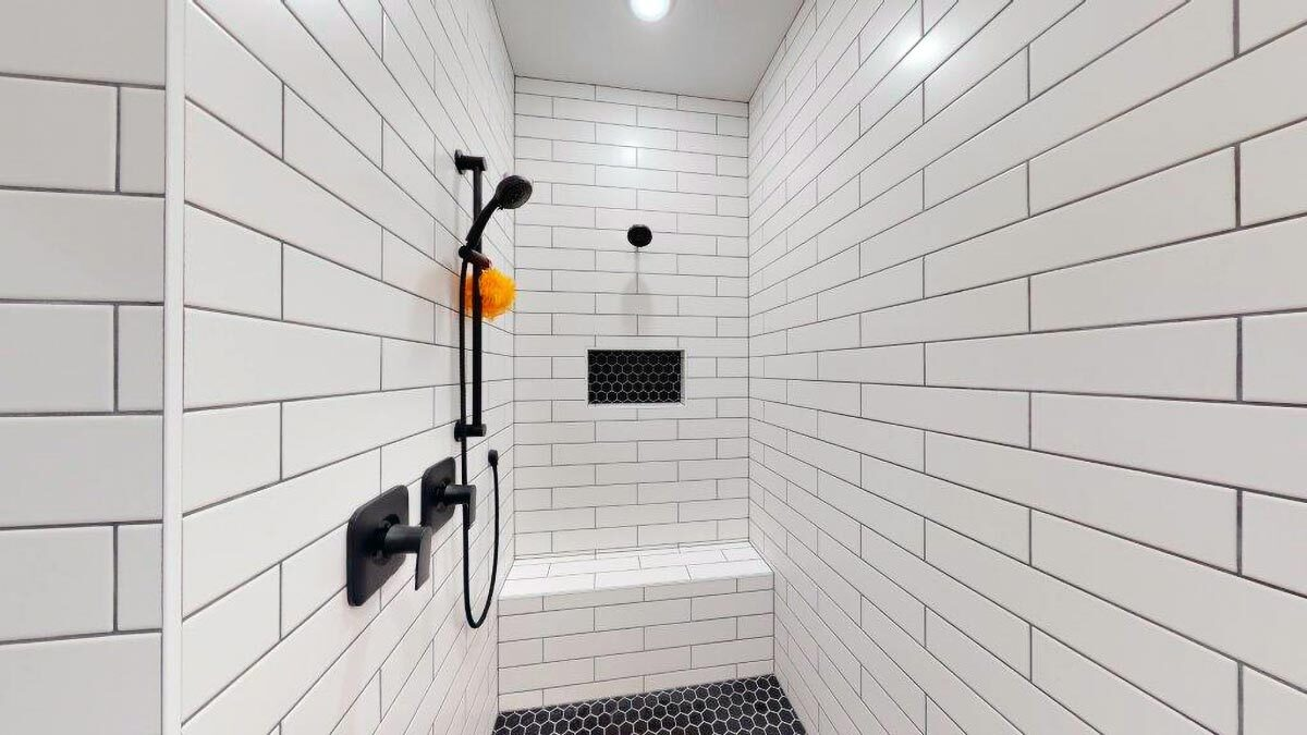 Walk-in shower with wrought iron fixtures, a built-in bench, and white subway tile walls.