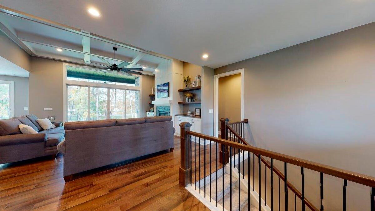 Across the living room is a carpeted staircase leading down the basement.