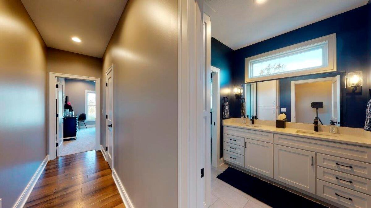A shared full bath with white vanity contrasted by the blue walls.