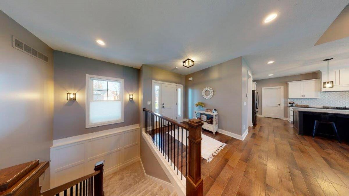 Foyer with a tasseled rug, white console, and entry door flanked by sidelights.