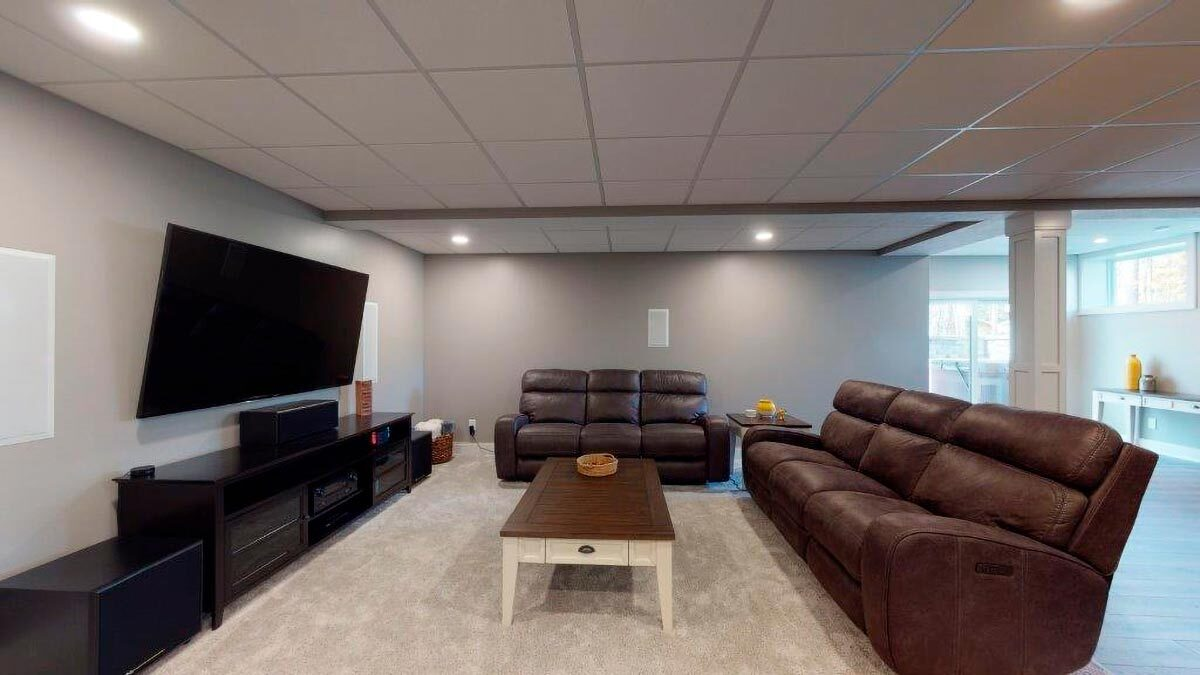 Recreation room with brown leather sectionals, a wooden coffee table, and a large flatscreen TV.