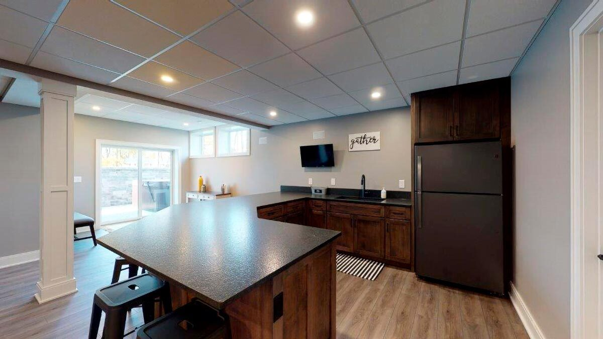 The wet bar has granite countertops, a fridge, and a sink.