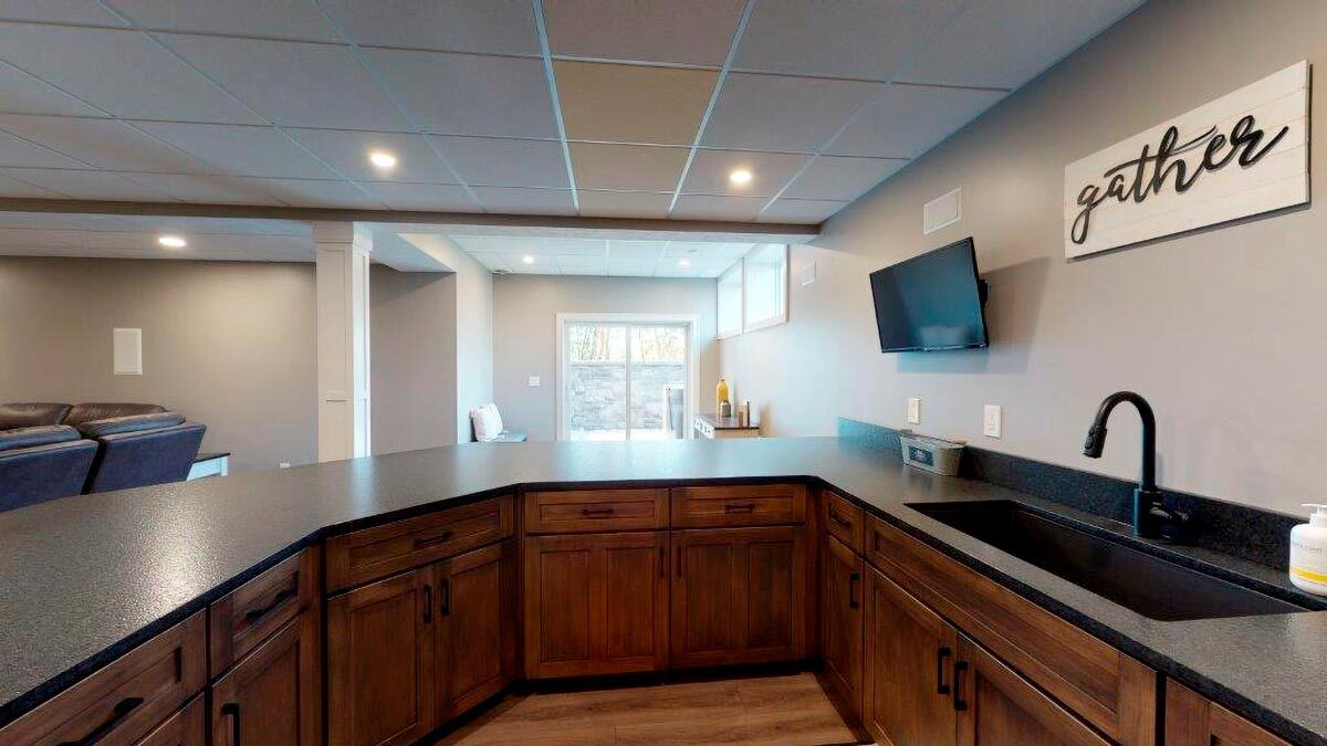 A closer look at the wet bar shows the undermount sink and wall-mounted TV.
