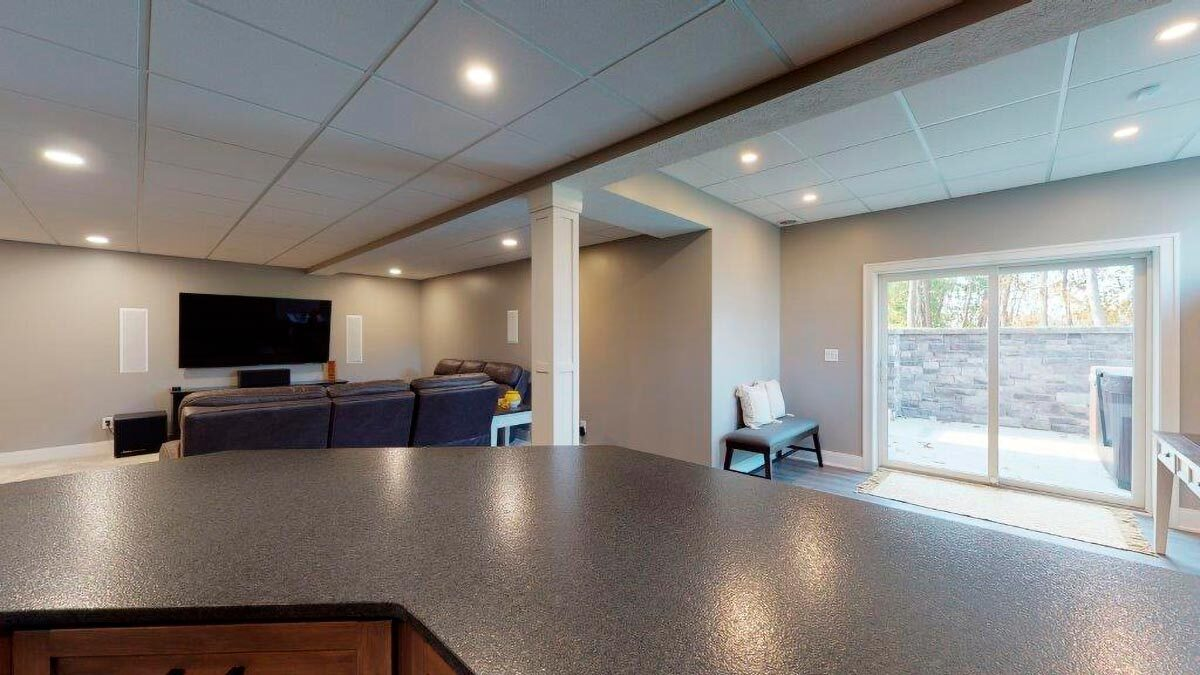 The recreation room extends to an open patio via sliding glass doors.