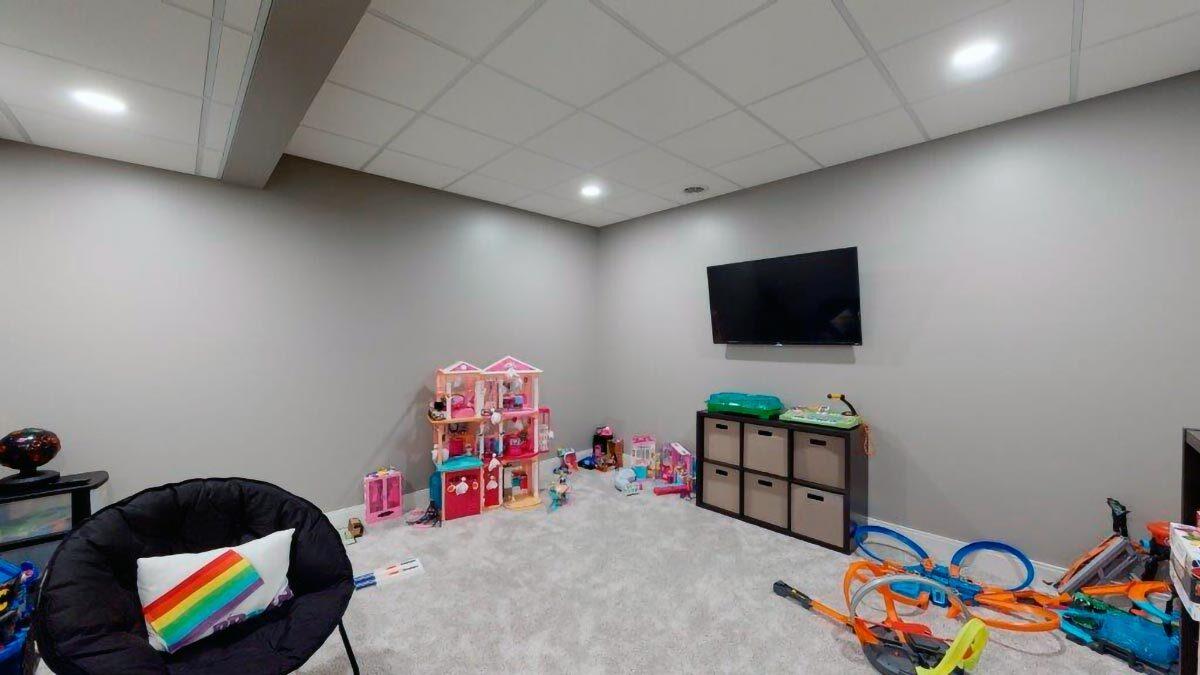 Kid's playroom with carpet flooring, gray walls, and a wall-mounted TV.Kid's playroom with carpet flooring, gray walls, and a wall-mounted TV.