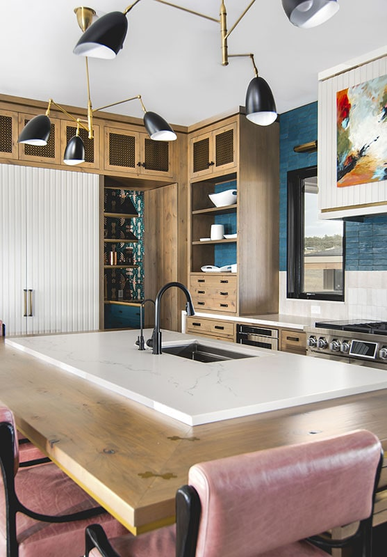 The kitchen features a large island with marble and wood countertops along with an undermount sink.