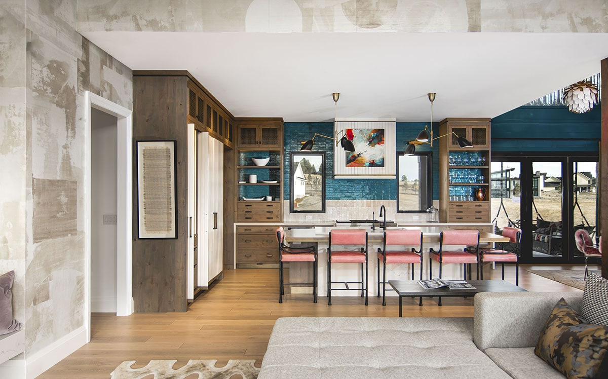 Pink counter chairs and blue-tiled backsplash add a splash of color to the kitchen.