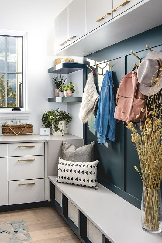 The mudroom is filled with white cabinets, black shelves, hooks, and a built-in storage bench.