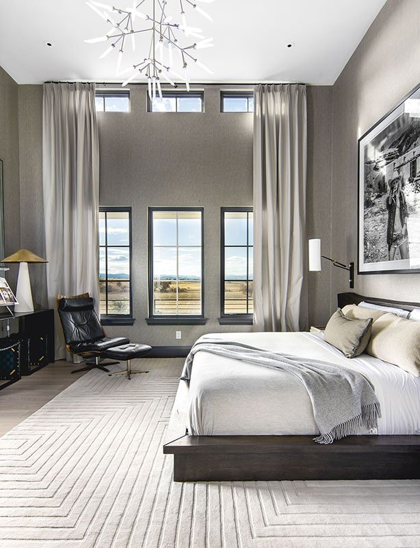 Primary bedroom with a platform bed, leather lounge chair, and a tall ceiling complemented with a statement chandelier.