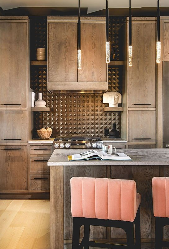 Kitchen with a center island and natural wood cabinetry accented with a decorative tile backsplash.