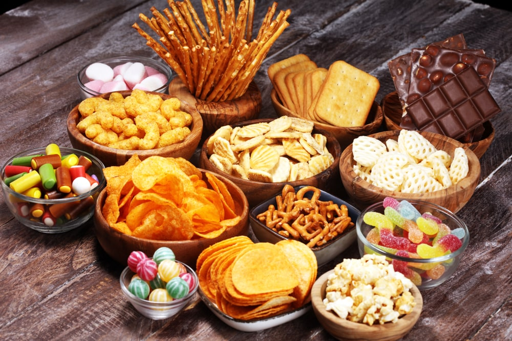 Bowls of assorted snacks on a wooden table.