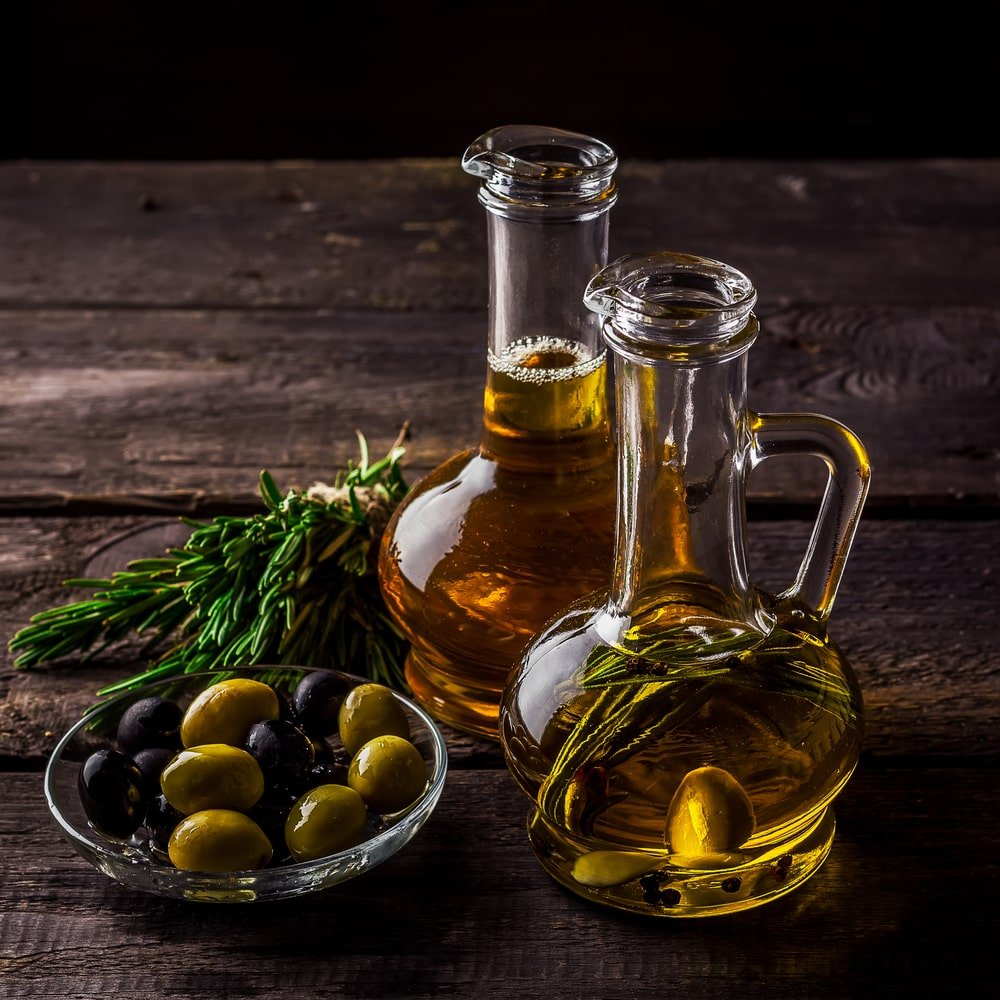 A glass bowl of fresh olive alongside a couple of bottles of olive oil.
