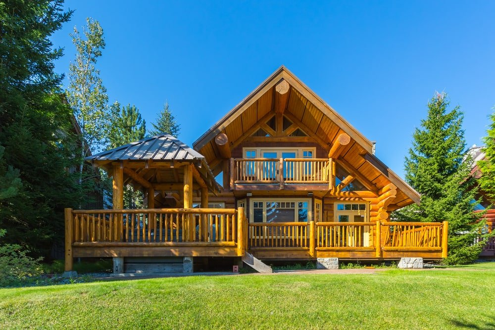 Mountain villa with log siding and covered porches.