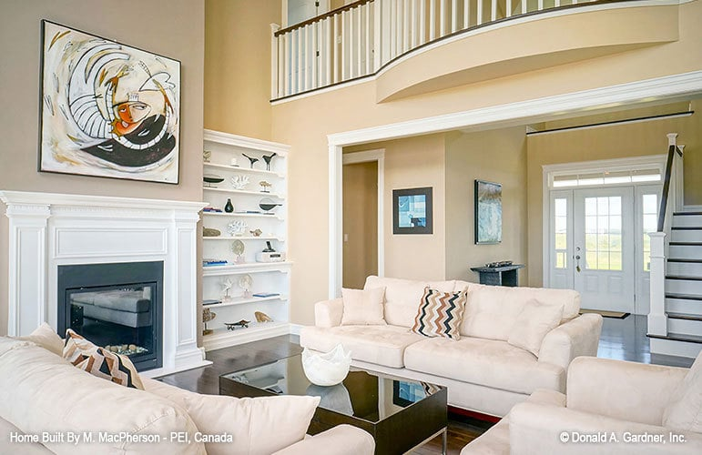 Living room with beige sofas, white built-ins, and a classic fireplace.