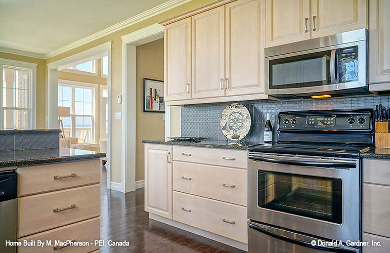 Kitchen with stainless steel appliances, light wood cabinetry, and a two-tier peninsula.