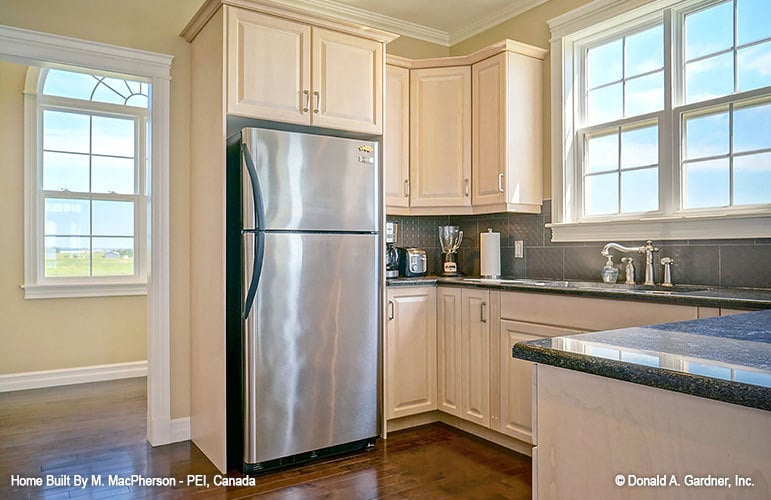 The kitchen includes a two-door fridge and an undermount sink placed under the window.