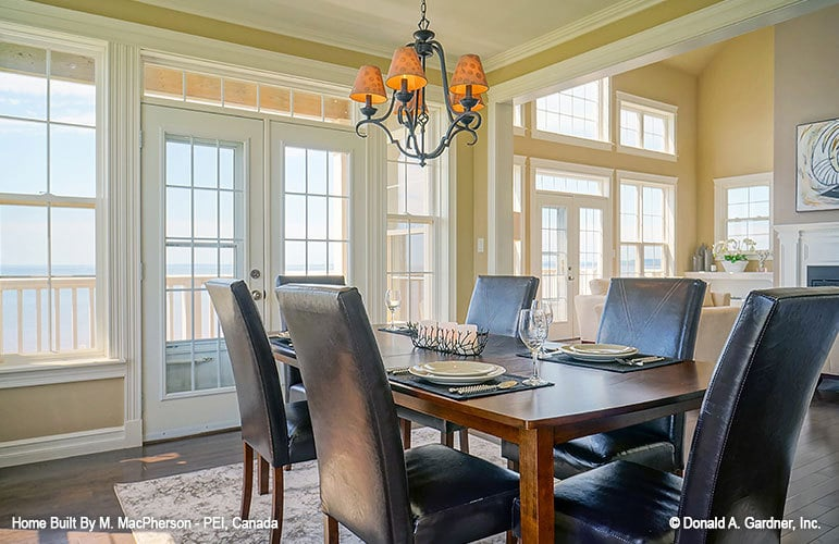 Dining area with a wooden dining table, leather upholstered chairs, and an ornate chandelier.