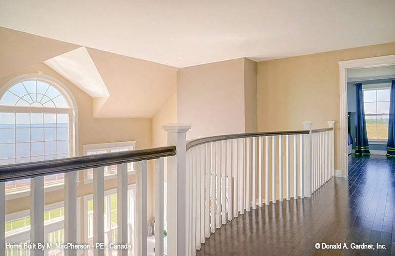 Balcony loft with white railings and dark hardwood flooring. It overlooks the living room below.