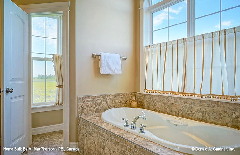 There's also a deep soaking tub clad in beige marble tiles.