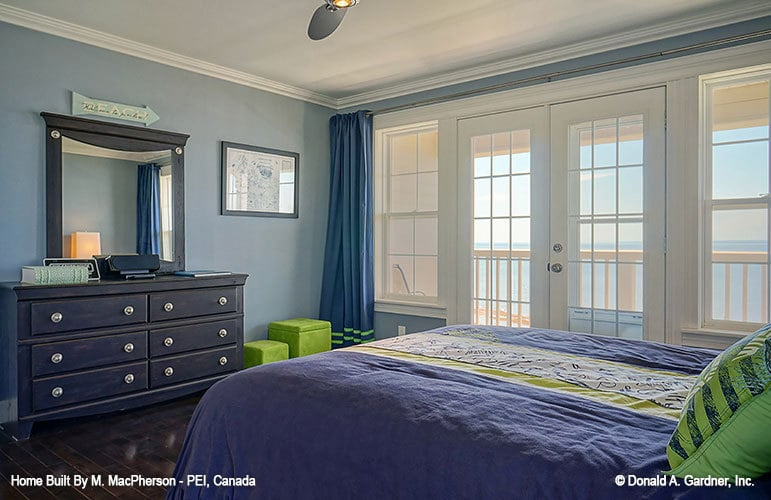 Another bedroom with a balcony, blue walls, a black dresser, and a dark hardwood floor.