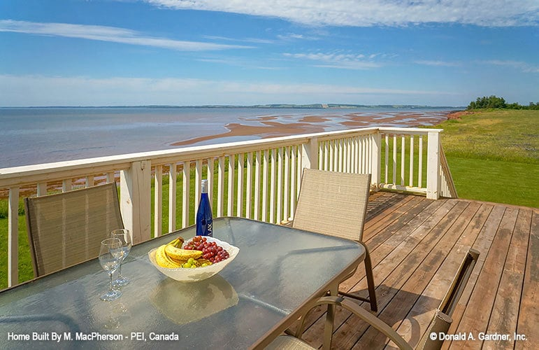 Rear deck with white railings and outdoor dining set. It has an amazing view of the beach.