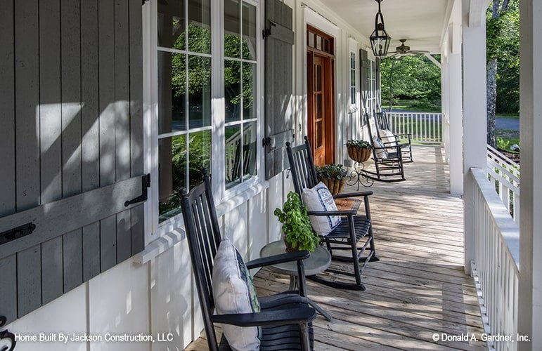 The entry porch is filled with wooden rocking chairs, round side tables, and ornate flower pedestals.