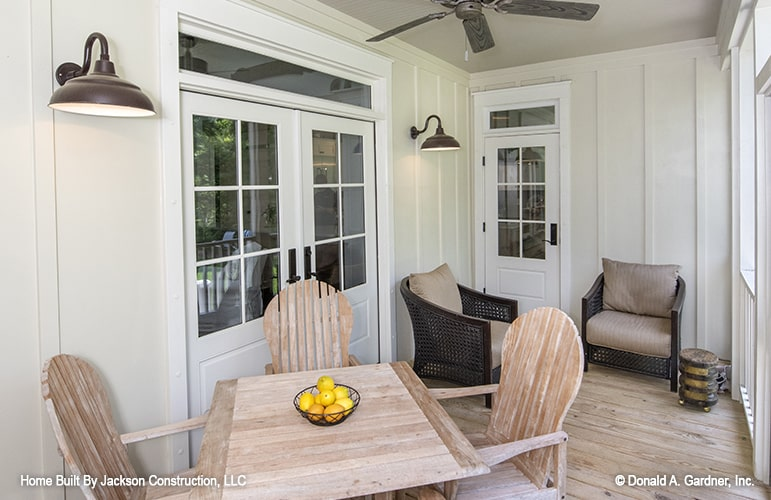 Screened porch with cushioned wicker chairs and a wooden dining set.