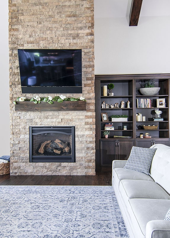 A closer look at the fireplace topped with a wall-mounted TV.