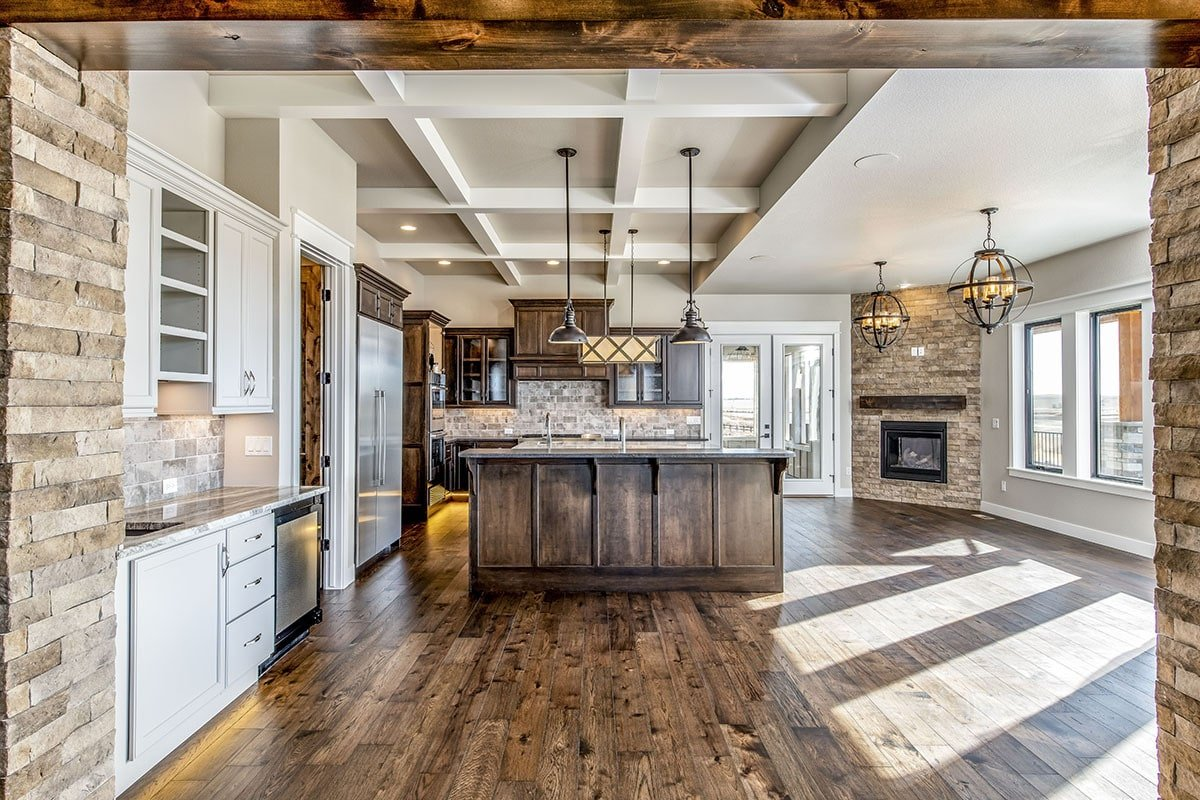 The kitchen has a coffered ceiling, wooden cabinetry, a corner fireplace, and plenty of counter space.