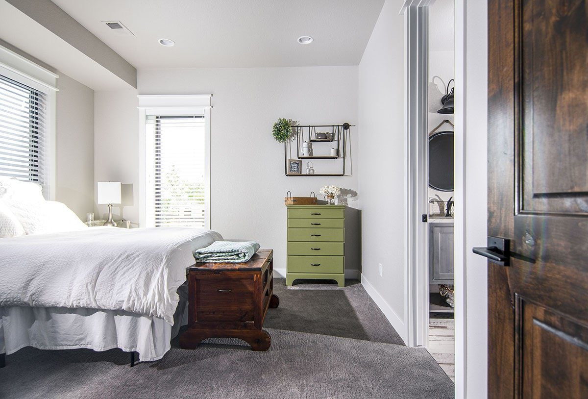 This bedroom has carpet flooring, a green dresser, and a skirted bed with a wooden storage bench at its end.