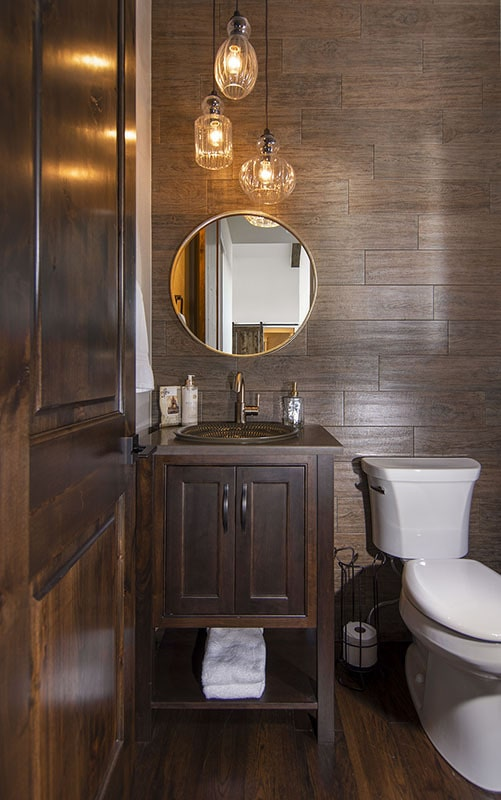 Powder bath with a toilet and a wooden vanity paired with a round mirror.