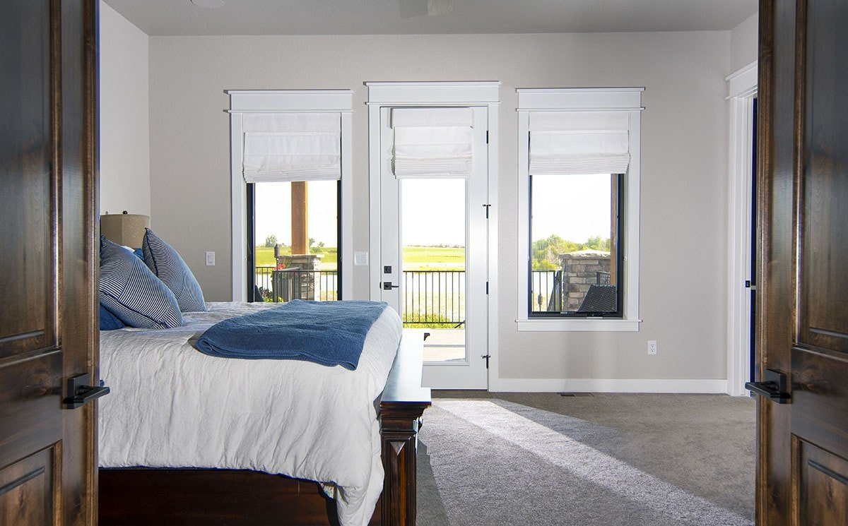 Primary bedroom with a cozy wooden bed and a private deck accessible via a glass door.