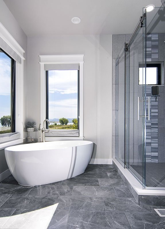 The primary bathroom offers a freestanding tub and a walk-in shower enclosed in frameless glass.The primary bathroom offers a freestanding tub and a walk-in shower enclosed in frameless glass.