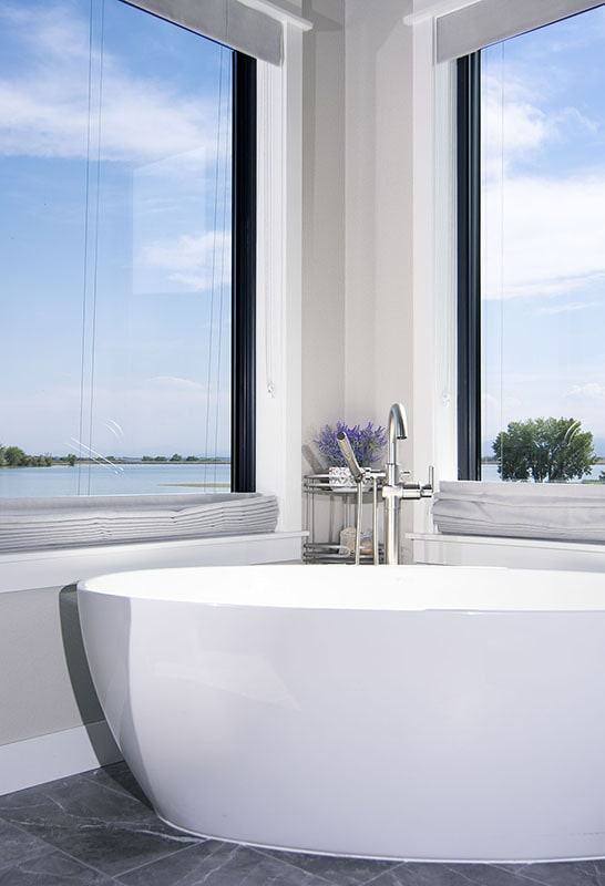 A closer look at the bathtub placed under the picture windows.