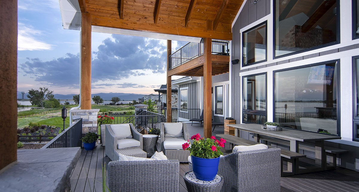 The covered porch is filled with an outdoor dining set and cushioned wicker seats.