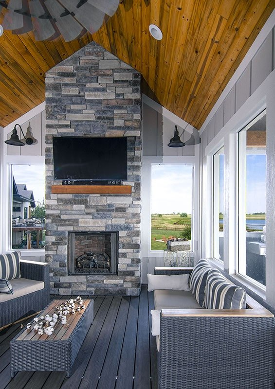 Screened porch with a cathedral ceiling, wide plank flooring, and a brick fireplace with a TV on top.