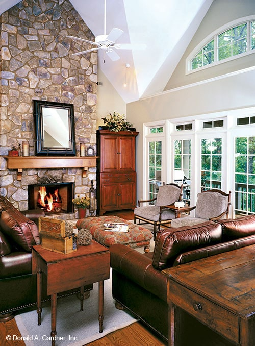 The great room has leather sofas, cushioned seats, a stone fireplace, and massive windows.