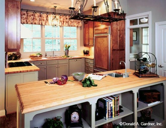 The kitchen offers a prep island, custom cabinetry, wooden countertops, and a wrought iron chandelier.