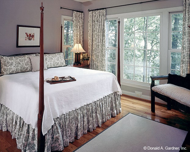The primary bedroom features a four-poster bed, a sitting area, and white framed windows dressed in patterned drapes.