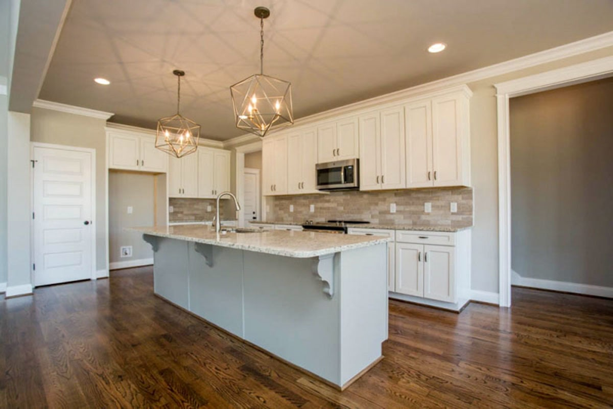 Kitchen with white cabinetry, stainless steel appliances, and a large island fitted with a sink.