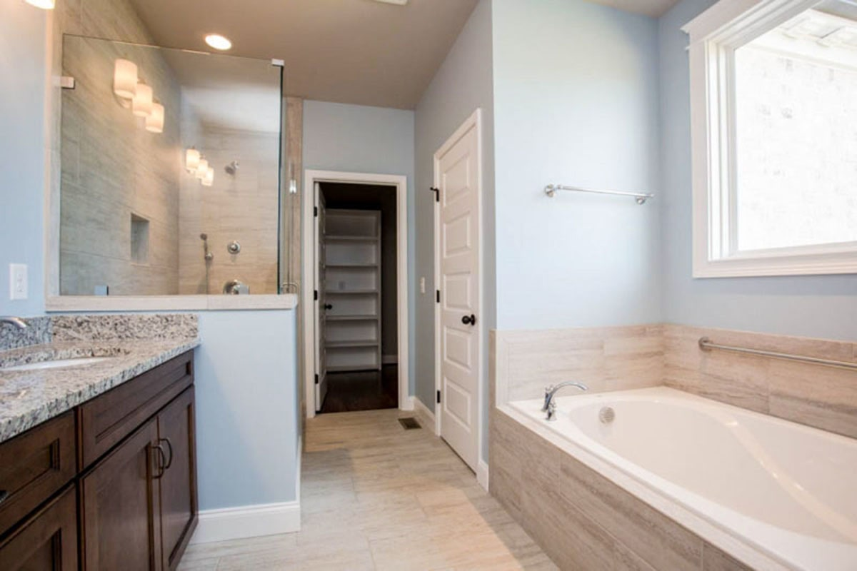 The primary bathroom is equipped with double vanity, deep soaking tub, separate shower, toilet room, and a walk-in closet.